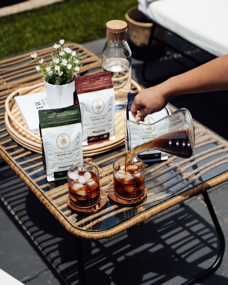 A carafe of specialty micro-lot iced coffee being poured from a Chemex brewer