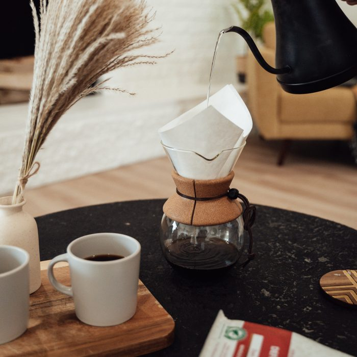 A chemex pour over coffee pot with a cup of fresh coffee in the foreground
