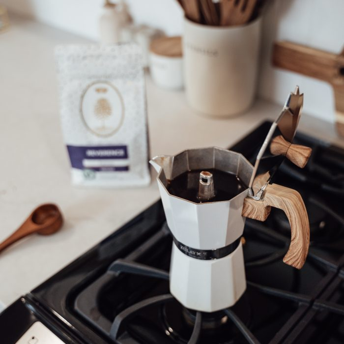 A Moka pot sitting on a gas range waiting to be brewed