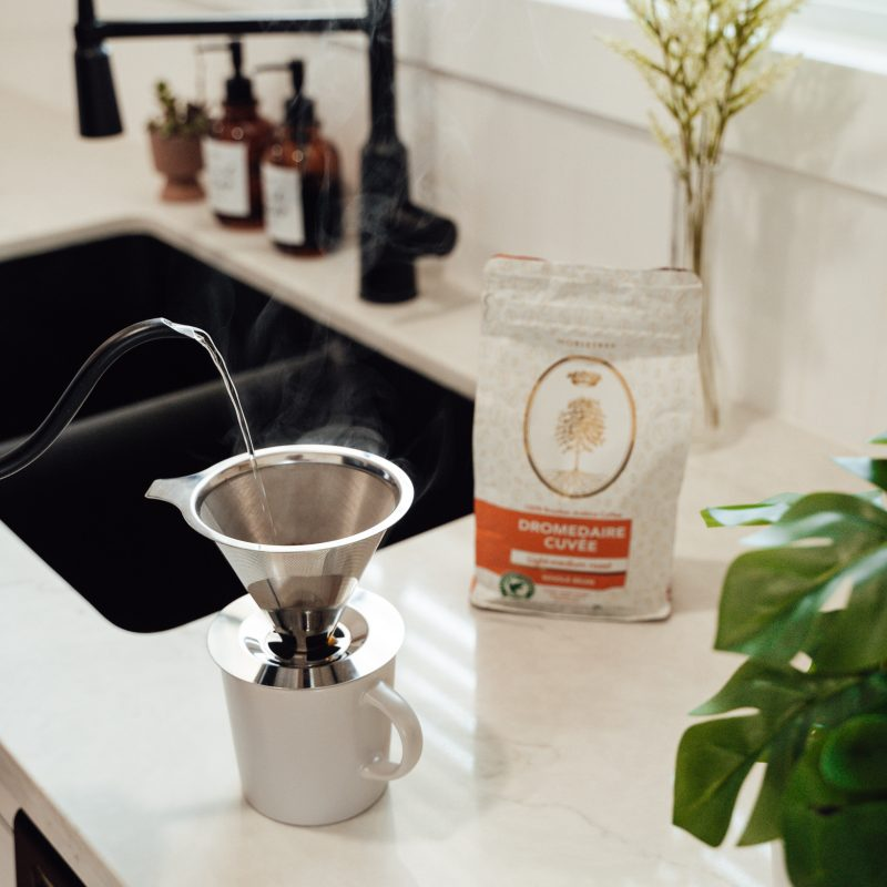 An individual slowly pouring water into a coffee cone utilizing the pour over coffee brewing method.